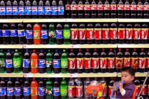 A boy sitting in a toy tricycle is pushed past shelves of bottled beverages at a supermarket in Nanjing