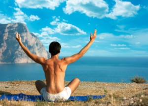 Man Doing Yoga at the Sea and Mountains